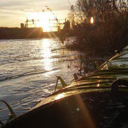 Zachodzące słońce nad rzeką widok z brzegu